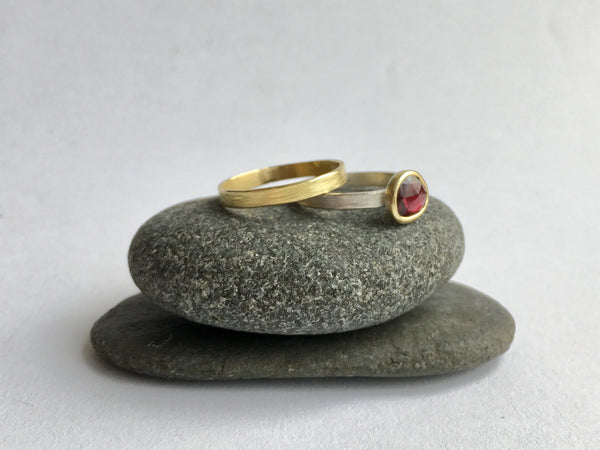 Gold wedding band with Mozambique garnet set in 18 ct gold on silver hammer band sitting on two grey stones on www.wyckoffsmith.com