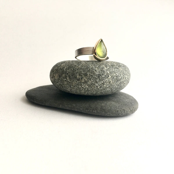 Pear shaped green idiocrase ring on top of two pebbles on www.wyckoffsmith.com