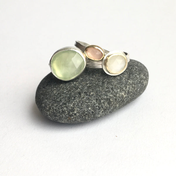 Assortment faceted gemstone silver and gold stacking rings on a pebble by Michele Wyckoff Smith - left to right: prehnite, peach moonstone, white moonstone