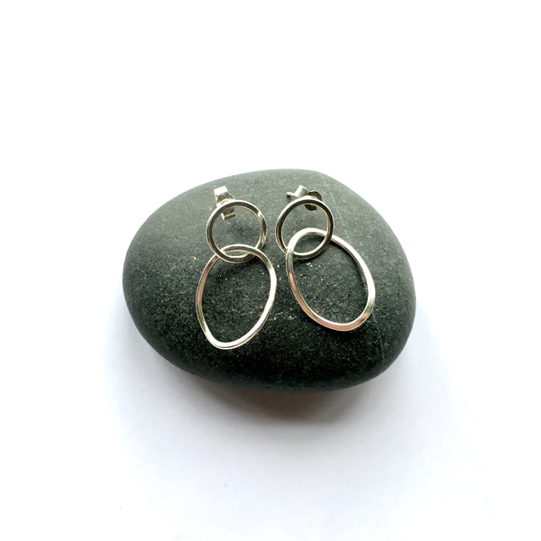 Small silver Twisted Petal Earrings sitting on top of a pebble  on www.wyckoffsmith.com