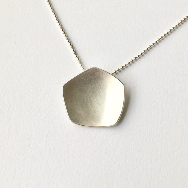 Inspired by the calyx of the poppy head, this abstract silver pendant is by Michele Wyckoff Smith