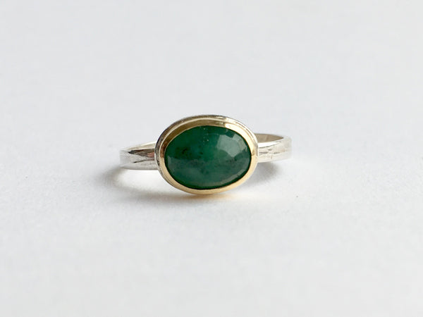 Emerald ring with dark inclusions set in 18 ct gold on silver band by Wyckoff Smith Jewellery
