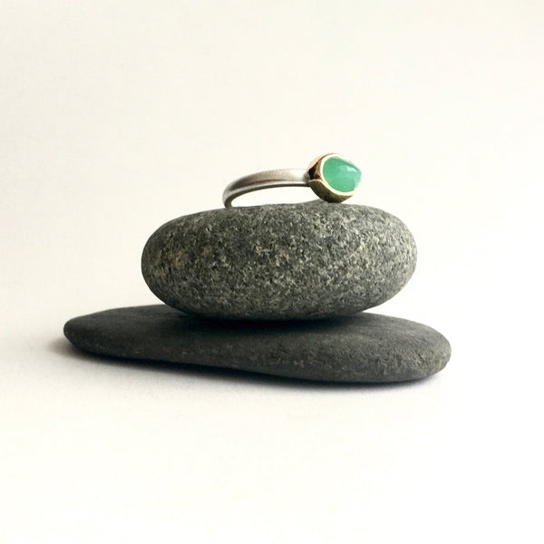 Side view of faceted chrysoprase set in 18 ct gold on a silver ring on two pebbles  available on www.wyckofsmith.com