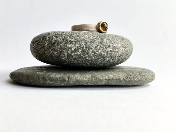 Smokey topaz silver and gold stacking ring perched on two granite pebbles by Wyckoff Smith Jewellery