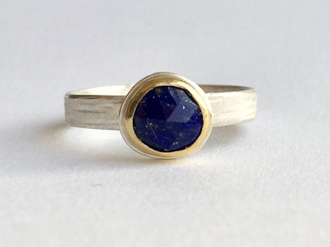 Raw faceted lapis lazuli round stone with flecks of gold in gold bezel setting on a silver ring. Wyckoff Smith Jewellery