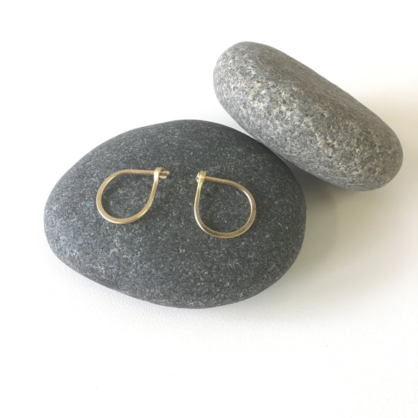 Two hand forged 18 ct gold hoop earrings on a black stone - Wyckoff Smith Jewellery