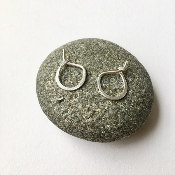 Small hand forged silver hoop earrings on a stone - Wyckoff Smith Jewellery