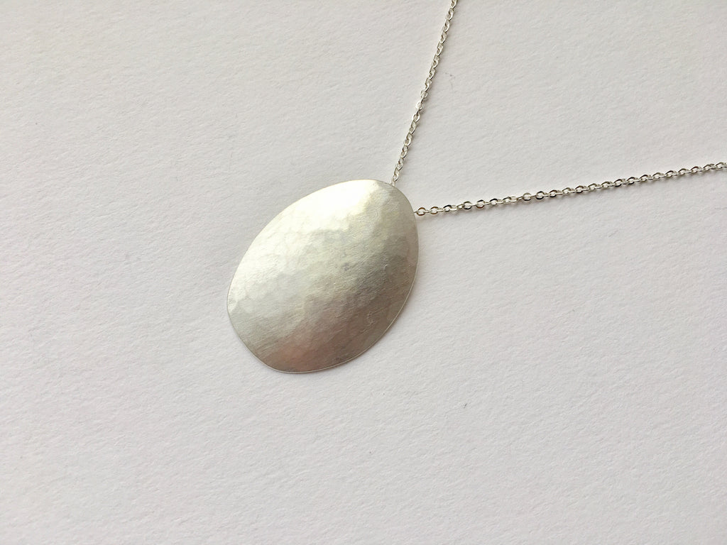 Convex egg shaped oval with light hammered texture and matte finish by Wyckoff Smith Jewellery.