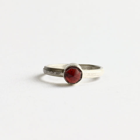 Faceted red garnet on a hammered texture silver band by Wyckoff Smith Jewellery