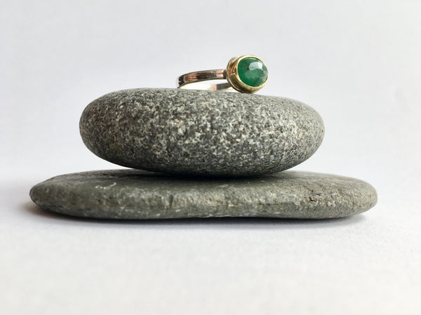 Emerald ring sitting on two granite pebbles by Michele Wyckoff Smith