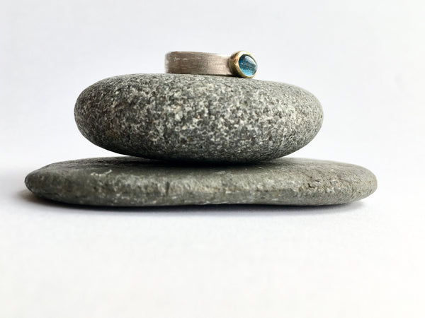 Tourmaline silver and gold stacking ring on top of garnet pebbles by Michele Wyckoff Smith