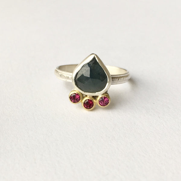 Blue green faceted sapphire ring with rhodolite garnets set in 18 ct gold. Wyckoff Smith Jewellery