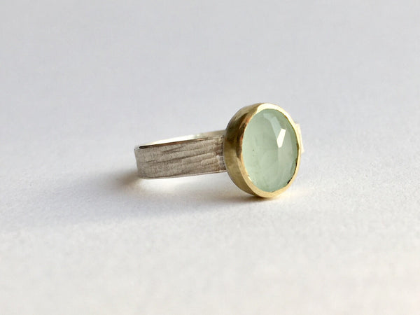 Faceted opaque aquamarine stone set in 18 ct gold bezel on a textured silver ring shank by Michele Wyckoff Smith