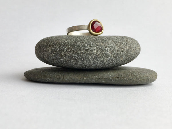 Silver and gold garnet ring on pictured on two pebbles by Wyckoff Smith Jewellery