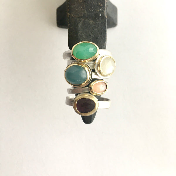 Top view of a collection of gemstone stacking rings on a miniature jeweller's anvil on www.wyckoffsmith.com top to bottom: chrysoprase, white moonstone, aquamarine, peach moonstone and pink tourmaline set in 18 ct gold on silver bands