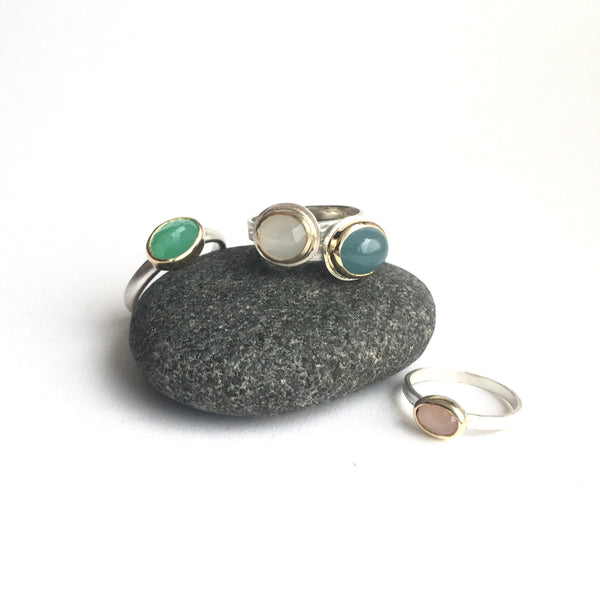 Assortment faceted gemstone silver and gold stacking rings on a pebble by Michele Wyckoff Smith - left to right: chrysoprase, white moonstone, aquamarine and peach moonstone