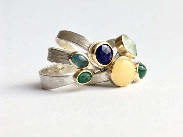 Jumble of silver and gold stacking rings by Michele Wyckoff Smith: emerald, tourmaline, lapis lazuli, butter yellow amber, aquamarine and emerald