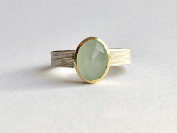 Front view of faceted aquamarine faceted gemstone set in 18 ct gold on textured silver ring band by Wyckoff Smith Jewellery