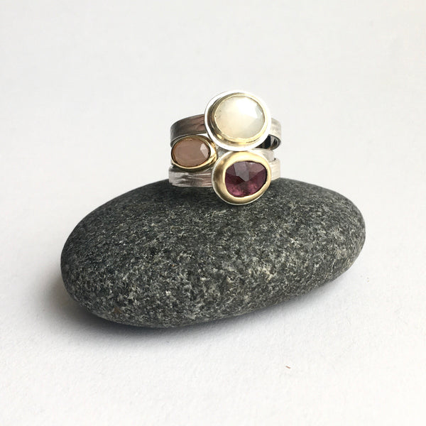 Stack of three gemstone rings on www.wyckoffsmith.com top to bottom: white moonstone, peach moonstone and tourmaline