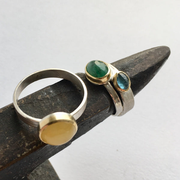 Gemstone silver and gold stacking rings on mini anvil: amber, emerald and tourmaline by Wyckoff Smith Jewellery