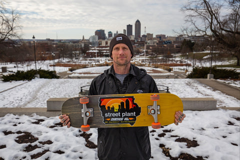 Pro skateboarder Mike Vallely holding up a Des Popsicle skateboard from Street Plant.
