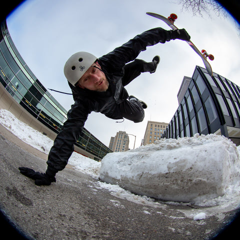 Pro skateboarder Mike Vallely doing a skateboard trick in Des Moines, Iowa with snow on the ground Winter 2021
