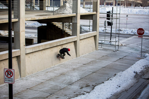 Pro skateboarder Mike Vallely skateboarding on a wall of a parking garage in Winter 2021 in Des Moines Iowa.