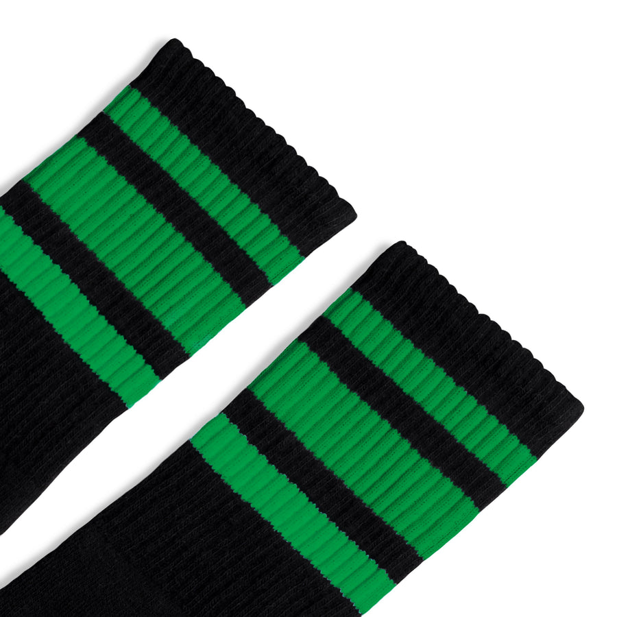 Black athletic socks with three green stripes for men, women and children.