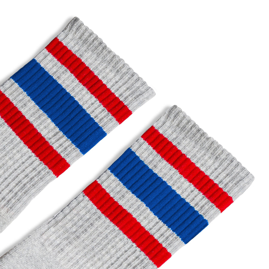 Grey athletic tube socks with red and blue stripes. Gray color.