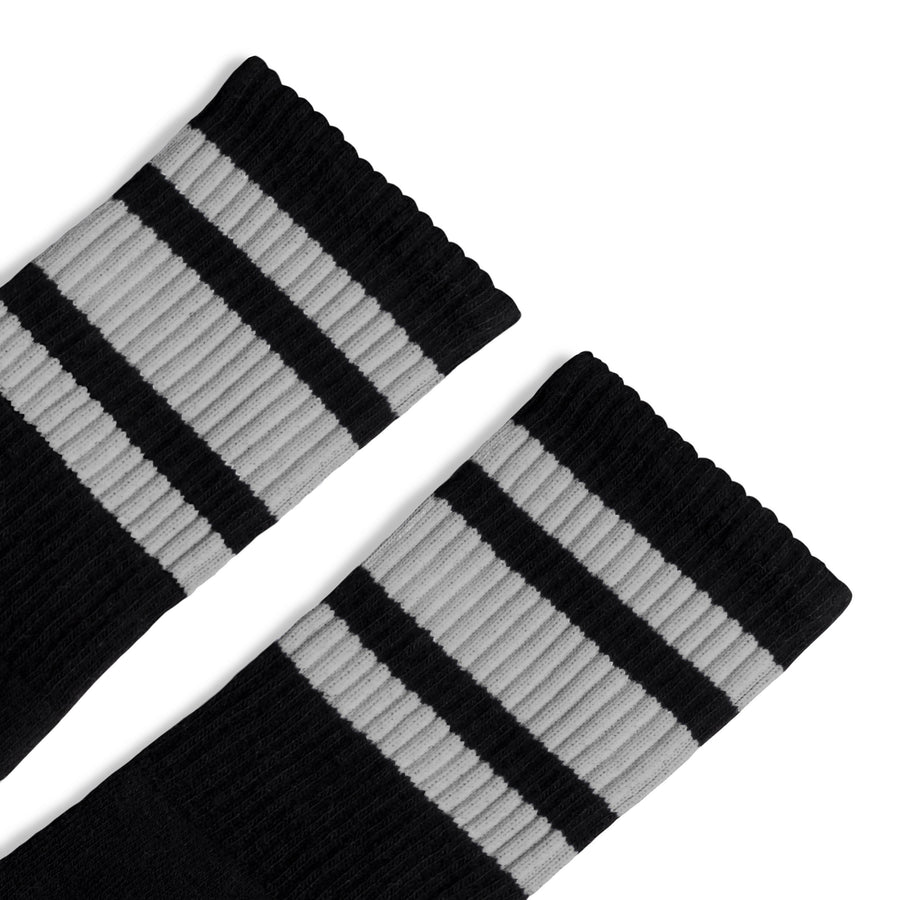 Black athletic socks with three grey stripes for men, women and children.