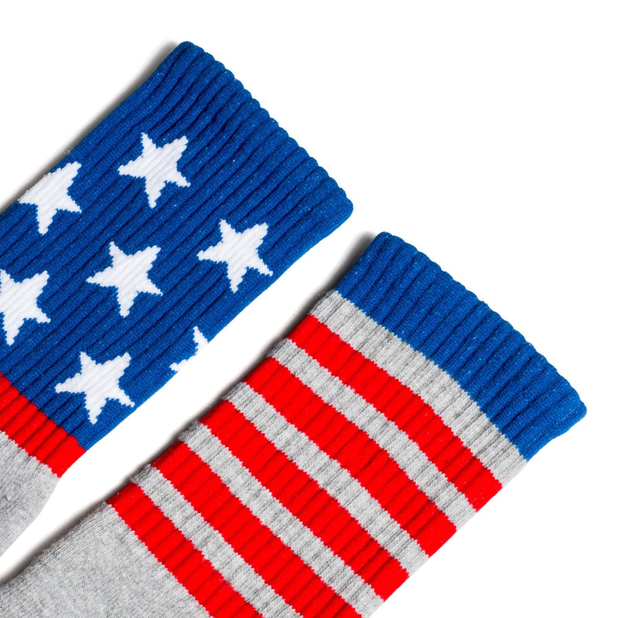 Heather Grey crew socks with American flag decorations with red stripes and white stars on a blue background for men, women and children.