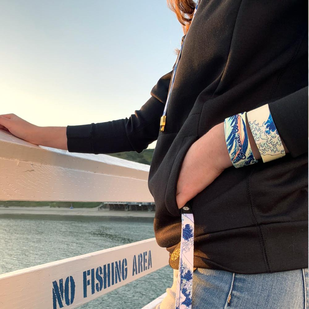 Lifestyle photo of girl holding a The Great Wave lanyard with the straps on her wrist showing the inside and outside of The Great Wave