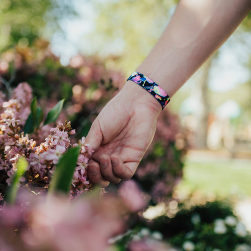 Lifestyle photo of hand holding flowers showing wrist with outside design of find bigger problems with neon geometric design overlaying a black background