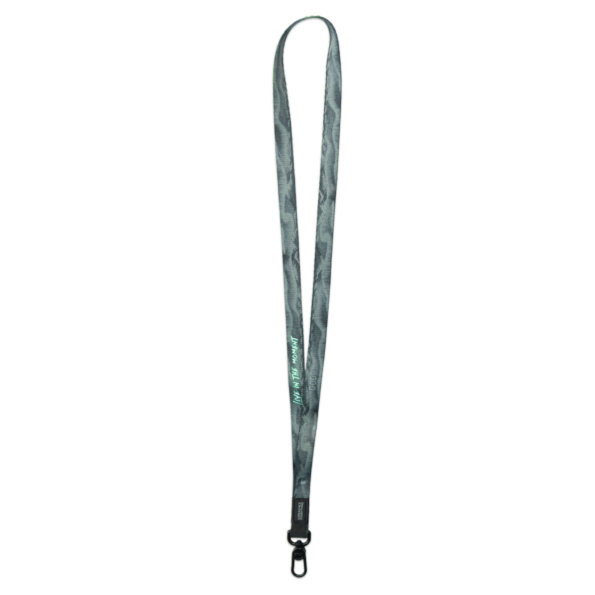 A product image of a ZOX lanyard showing the back of the design with a black colored metal clip. The lanyard is called and says Live In The Moment and the design is a grayscale version of the front design which is the northern lights