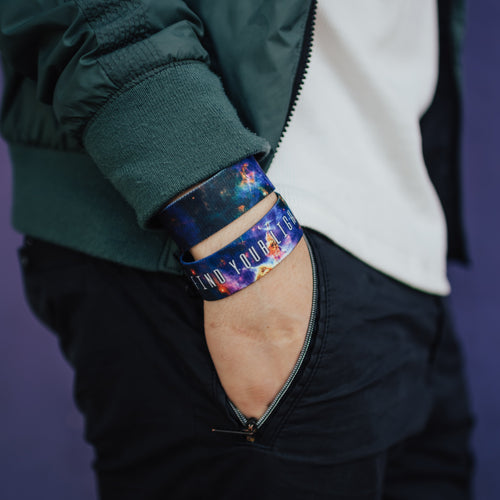 Lifestyle close up image of model's hand in their pocket and wearing two Find Your Light straps