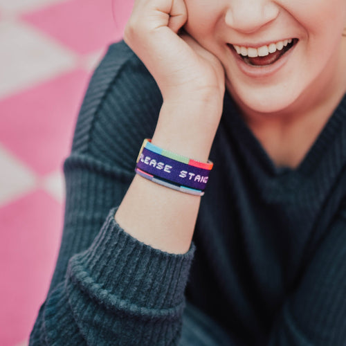 Lifestyle image of Please Stand By on wrist of smiling model