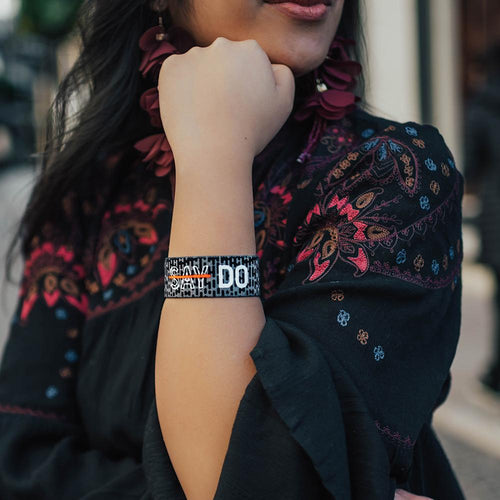 Lifestyle Image of Do on someone's wrist with a scarf in the background