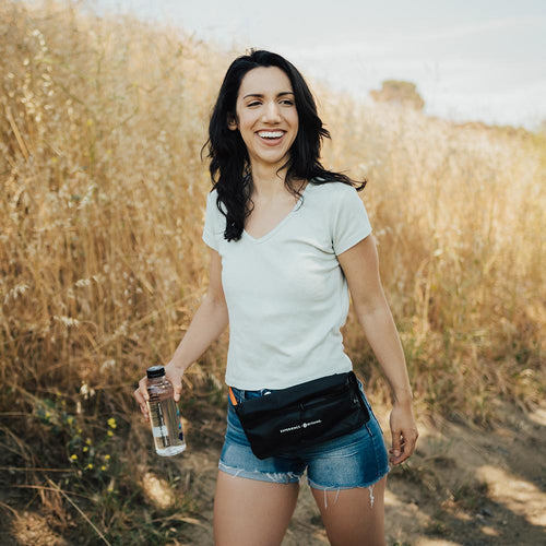 life style photo of a woman on a hike with the fanny pack around her waist with a water bottle in her hands