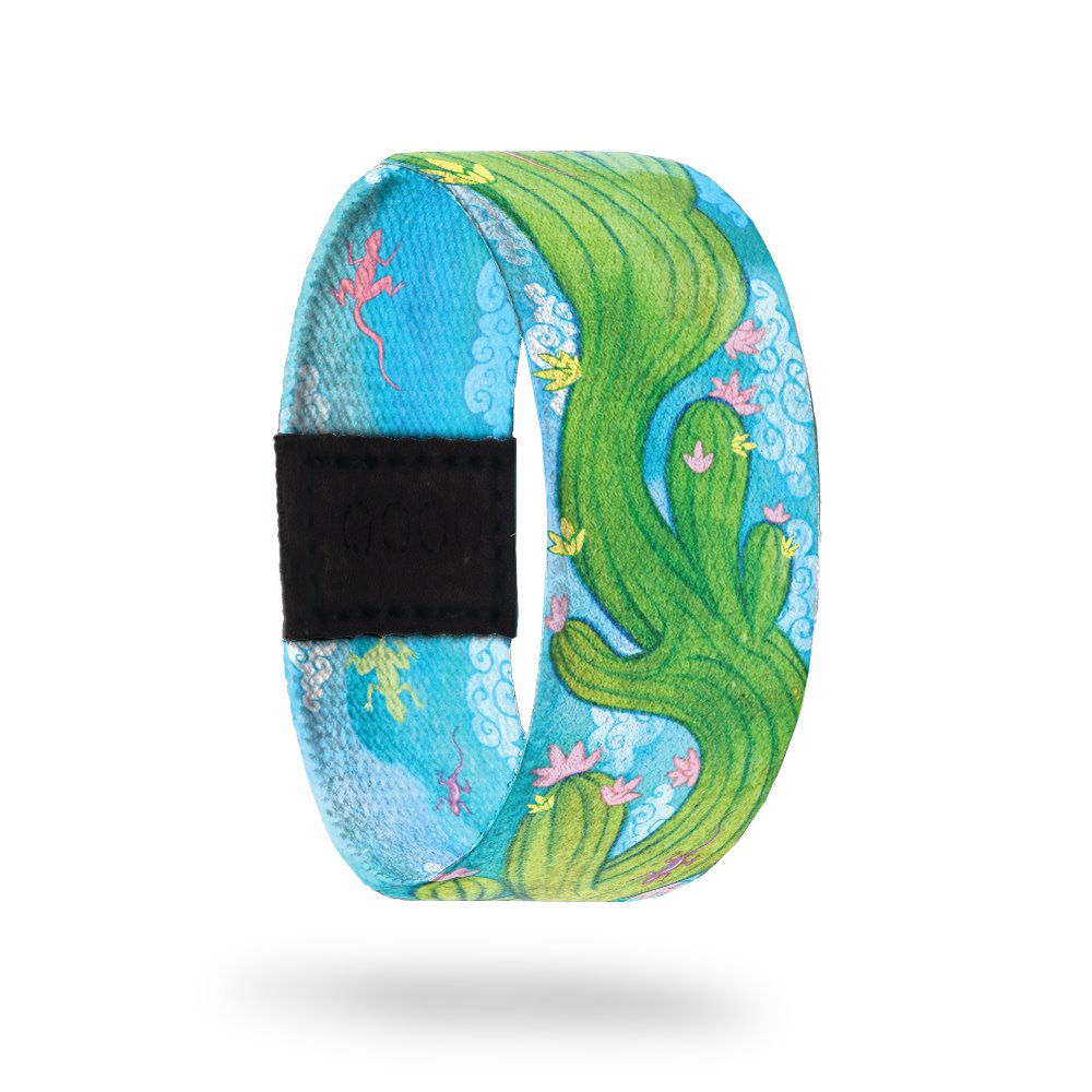 Outside Design of Endurance: light blue sky background with green cactus with pick and yellow flowers waving through the center of the strap