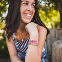 Lifestyle image close up of someone smiling with 2 Stay Positive on their wrist