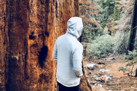 Young Male from the back with his hood up wearing a grey imperial zip hoodie while walking in a forest and is next to a large tree