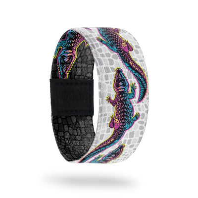 product image of the outside of a wristband called Make your Own Path. The background is a white and grey version of alligator scales. On top are multi-color alligators one after another for the entire design. Each alligator is a gradient that is pink, yellow, and blue
