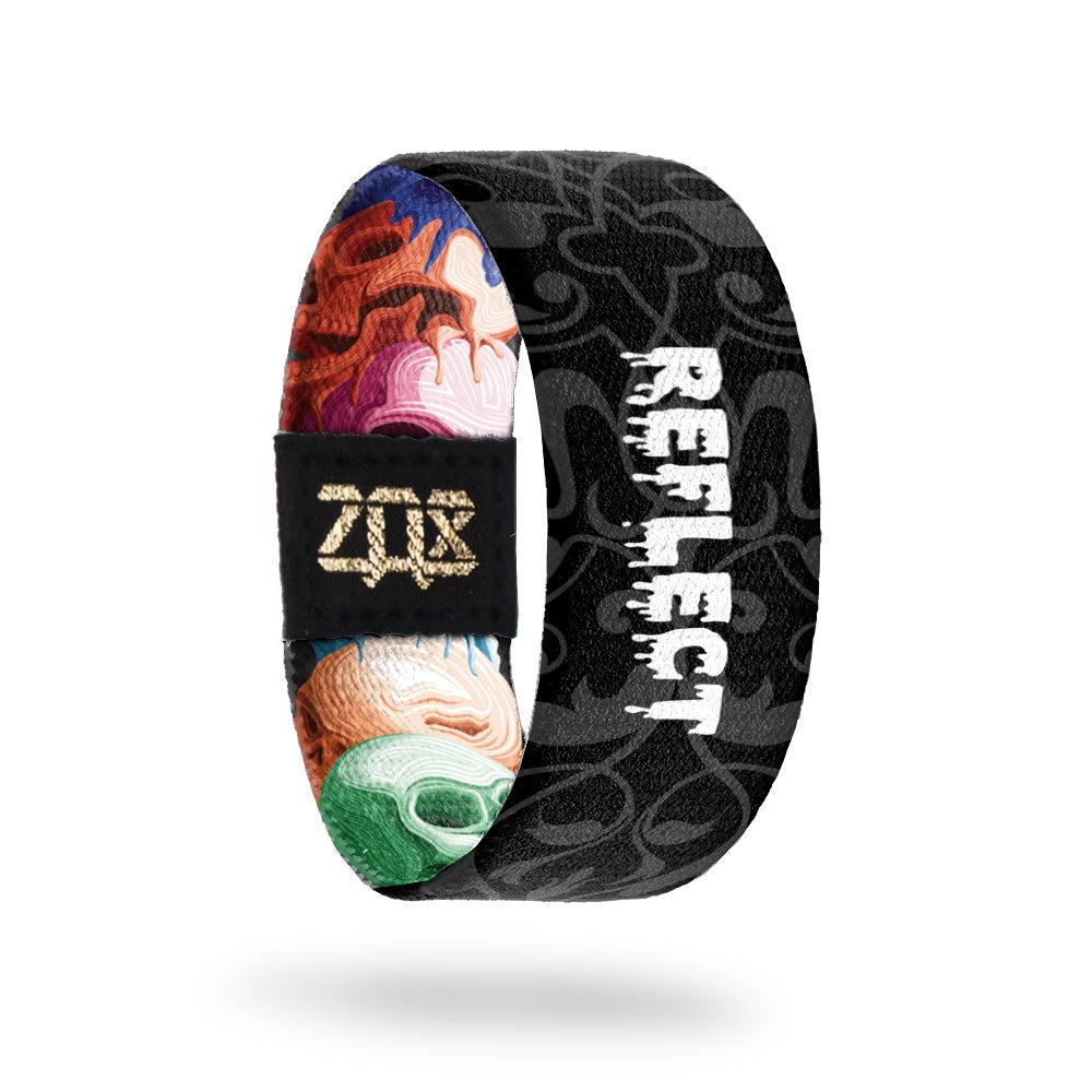 inside of the wristband with the type Reflect on it. Background is a black and white version of the hand drawn skulls