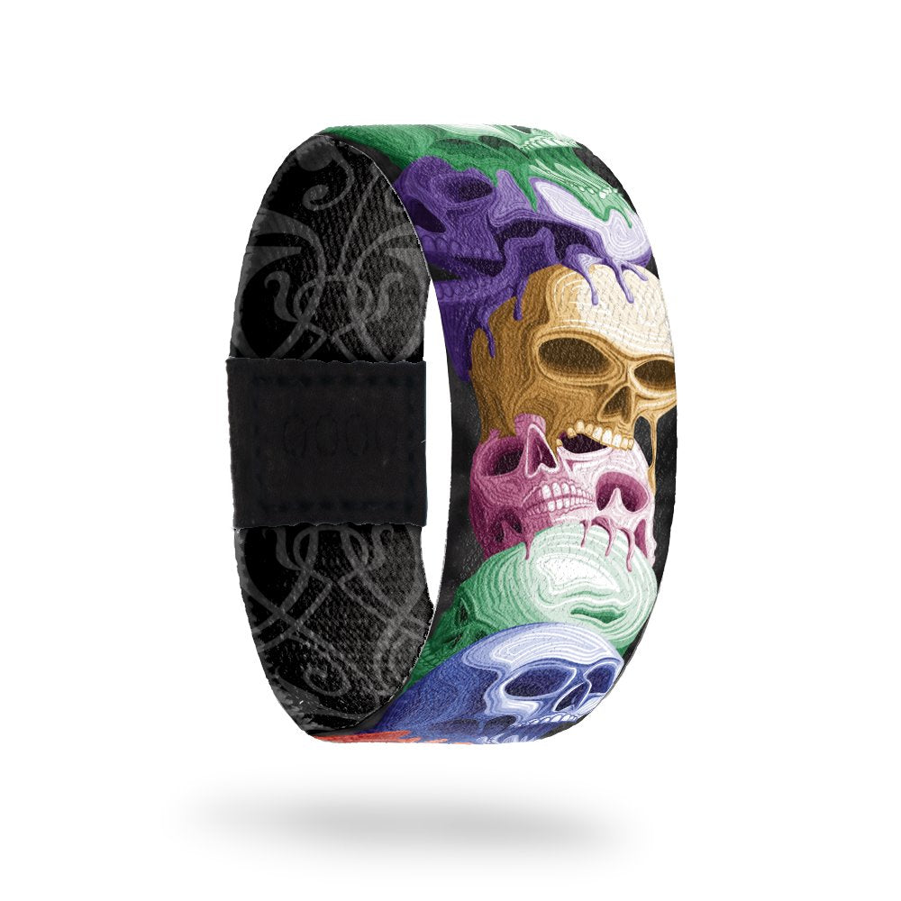 product image of front of wristband named Reflect. The design is a stack of hand drawn skulls in different colors such as purple, gold, pink, blue, and green
