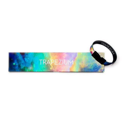 Studio image of Trapezium clasped together laying on the box it comes in, which has a design of  a multi-colored light space background and Trapezium centered in white text