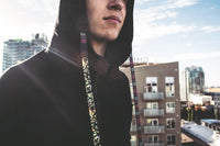 Young Adult male with hood up switching out the interchangeable strings from one design to another with a city skyline in the back