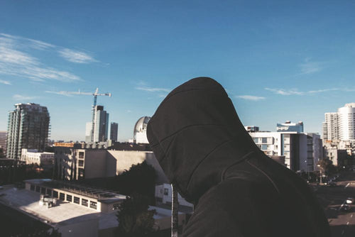 This is an image of a person from the side wearing the zipper Imperial Hoodie with the hood up looking at a skyline