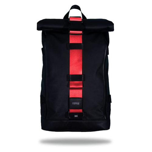 Product image of an Imperial backpack showing a wide strap down the center of it that is interchangeable. The closure strap the item that is for sale on this page and is called Grapefruit and is a solid red with orange undertones color