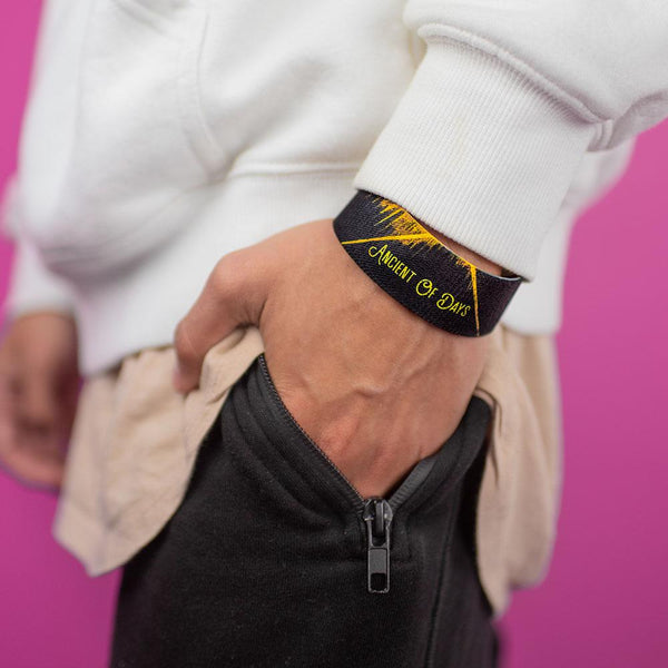 Studio image of hand in pants pocket wearing Ancient Of Days on their wrist