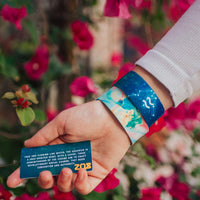 Close up image of hand holding a card with a quote on it and two Aquarius straps on their wrist